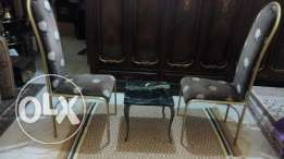 Two metal chairs golden color with table and carpet