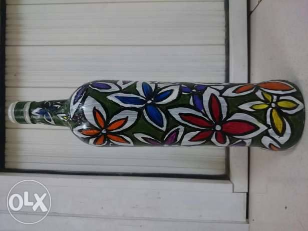 Painting of flowers on long glass bottle