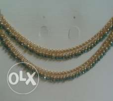 Anklet with green crystals and golden beads.