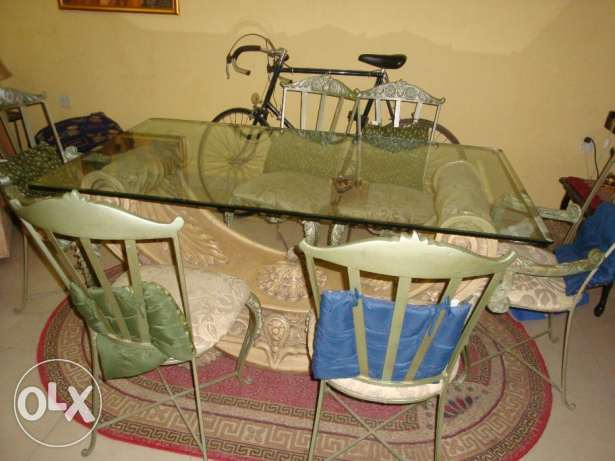 Glass table on gypsum base and six iron chairs